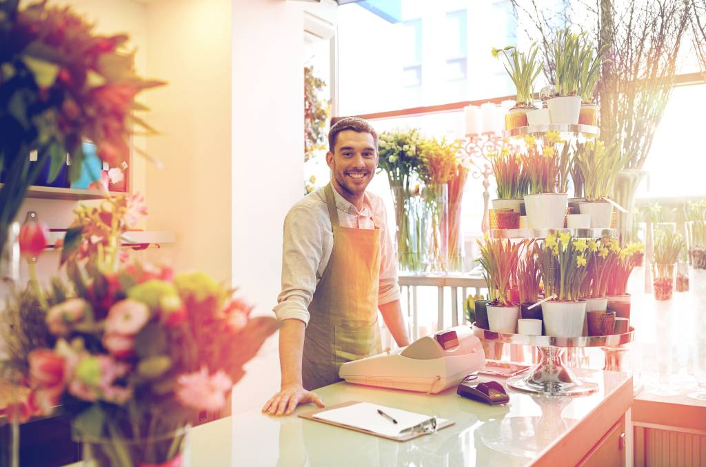 florist man with clipboard at flower shop counter